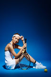 Portrait of a female tennis player with racket and ball sitting on floor in studio Royalty Free Stock Photo