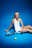Portrait of a female tennis player with racket and ball sitting on floor in studio Royalty Free Stock Photography