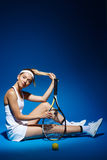 Portrait of a female tennis player with racket and ball sitting on floor in studio Royalty Free Stock Images