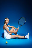 Portrait of a female tennis player with racket and ball sitting on floor in studio Stock Photo