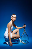 Portrait of a female tennis player with racket and ball sitting on floor in studio Stock Photography