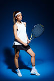 Portrait of female tennis player with racket posing in studio Stock Photo