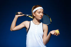 Portrait of female tennis player with racket on shoulder and ball in hand posing in studio Royalty Free Stock Images