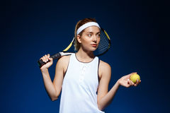 Portrait of female tennis player with racket on shoulder and ball in hand posing in studio Stock Photos