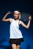 Portrait of female tennis player with racket on the shoulder posing in studio Stock Photo