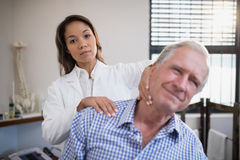 Portrait of female therapist giving neck massage to senior male patient. At hospital ward royalty free stock photography