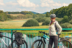 Portrait of female tourist cyclist standing on the bridge  on  b Stock Photos