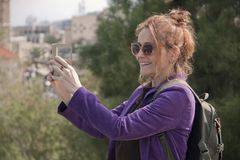 Portrait of a female tourist taking a photo on her smartphone stock photography