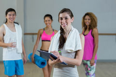 Portrait of female trainer holding clipboard with fitness class in background Stock Photography