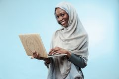 Portrait Of Female University Student Working on laptop. The beautiful young black african muslim girl wearing gray hijab at blue studio. She standing with royalty free stock photos