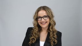 Portrait of female very rejoice and looking at camera at grey background. Portrait of female with curly hair in bussines suit, glasses very rejoice and looking stock video