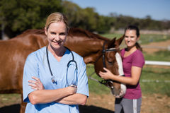 Portrait of female vet with woman standing by horse in background Royalty Free Stock Photo