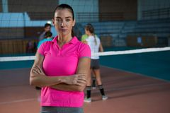 Portrait of volleyball player with teammates playing in background. Portrait of female volleyball player with teammates playing in background at court Stock Photo