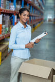 Portrait of female warehouse worker standing with clipboard Royalty Free Stock Photography
