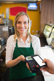 Portrait of female worker accepting payment through NFC Royalty Free Stock Image