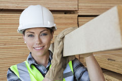 Portrait of female worker carrying wooden plank on shoulder Royalty Free Stock Photography