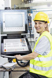 Portrait of female worker operating machinery at control panel in factory Stock Photo