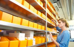 Portrait of a female worker organizing boxes on shelves Royalty Free Stock Photo