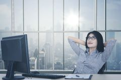 Female worker relaxing near the window. Portrait of female worker relaxing on the chair while daydreaming near the window. Shot in the office Royalty Free Stock Image