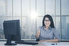 Female worker showing OK sign near the window. Portrait of female worker showing OK sign with her thumb while sitting near the window Royalty Free Stock Photography