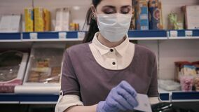 Portrait of female worker wearing a medical mask and gloves takes a Bank card from a customer and processes the online payment at