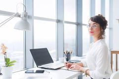 Portrait of a female writer working at office, using laptop, wearing glasses. Young employee planning her work day Royalty Free Stock Photography