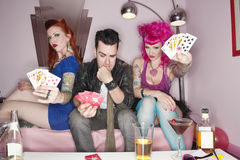 Portrait of females showing their playing cards while man thinking Stock Image
