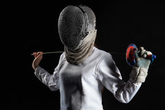 Portrait of fencer woman wearing white fencing costume practicing with the sword. Isolated on black background. Portrait of fencer woman wearing white fencing stock photography