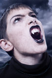 Portrait of fierce vampire with sharp long teeth. On stormy night Royalty Free Stock Images