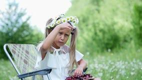Portrait Fille blonde, enfant, s'asseyant parmi des marguerites, dans un pré Ses cheveux sont décorés des marguerites Elle sourit banque de vidéos