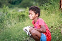 Portrait fille de tribu d'Aeta de petite avec son bâti proche de chat mignon Photographie stock libre de droits