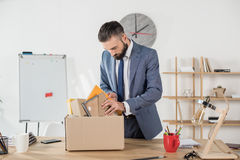 Fired sad businessman packing office supplies at workplace. Portrait of fired sad businessman packing office supplies at workplace Royalty Free Stock Image
