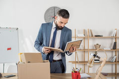 Fired upset businessman looking at photos at workplace in office Royalty Free Stock Photography