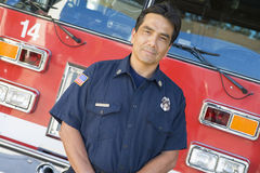 Portrait of a firefighter by a fire engine.  Royalty Free Stock Images