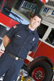 Portrait of a firefighter by a fire engine.  Royalty Free Stock Photography