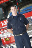 Portrait of a firefighter by a fire engine.  Stock Photos