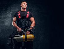 Portrait of a firefighter man holding an oxygen tank and looking sideways. Studio photo against a dark textured wall royalty free stock photo
