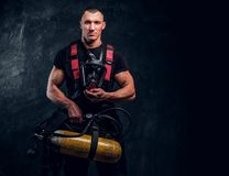 Portrait of a firefighter man holding an oxygen tank and mask, looking at a camera. Studio photo against a dark textured wall stock photo