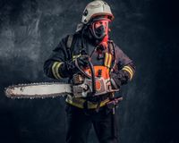 Portrait of a firefighter in safety helmet and oxygen mask holding a chainsaw. Studio photo against a dark textured wall. Firefighter in safety helmet and oxygen stock photos