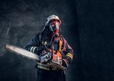 Portrait of a firefighter in safety helmet and oxygen mask holding a chainsaw. Studio photo against a dark textured wall. Firefighter in safety helmet and oxygen royalty free stock photo