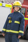 Portrait of a firefighter standing. In front of a fire engine Stock Images