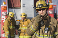 Portrait Of A Firefighter Talking On Radio. Portrait of a middle aged firefighter talking on radio with colleagues standing in the background Royalty Free Stock Photo