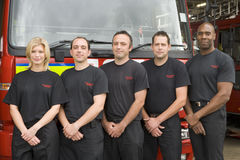 Portrait of firefighters standing by a fire engine.  Royalty Free Stock Image