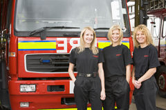 Portrait of firefighters standing by a fire engine stock images