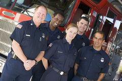 Portrait of firefighters standing by a fire engine Royalty Free Stock Photo