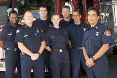 Portrait of firefighters standing by a fire engine. Smiling stock photo
