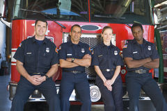 Portrait of firefighters standing by a fire engine stock image