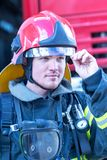 Portrait of a fireman. With car on background Stock Image