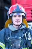 Portrait of a fireman. With car on background Royalty Free Stock Images