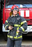 Portrait of a fireman. With car on background Royalty Free Stock Photos